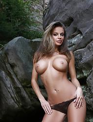 Sexy slim babe Dana Harem posing nude outdoors on a rock